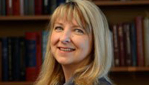 A headshot photo of Dr. Christine Polimeni smiling with book shelves in the background.