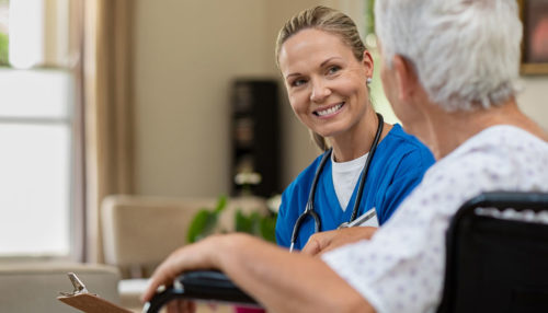 A smiling nurse consults with an elderly patient.