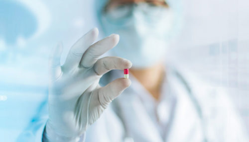 A doctor wearing a surgical mask holds a small red and white pill capsule out.